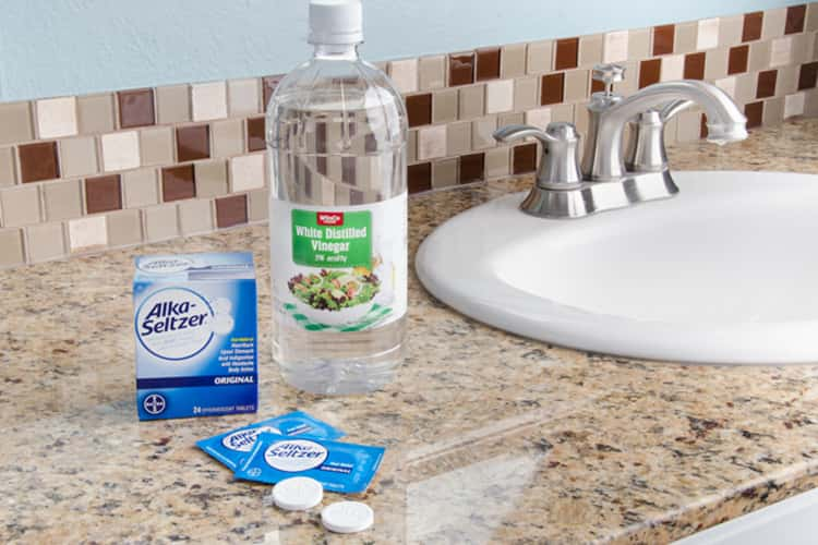 A photo of alka-seltzer tablets and a bottle of white vinegar beside a sink