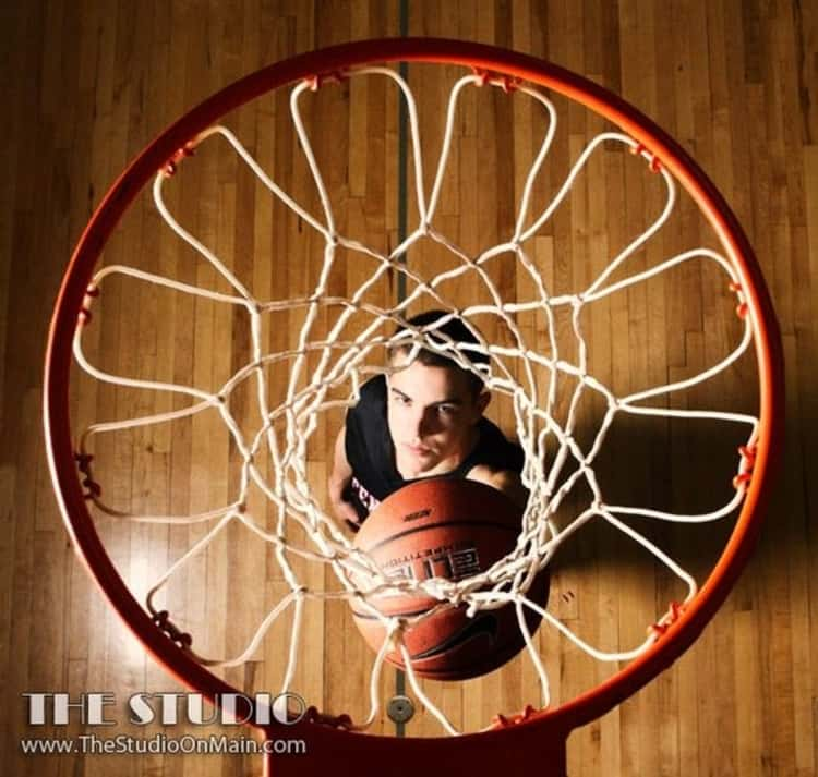 senior picture idea for guys - photo taken from above a basketball hoop of guy looking up and holding basketball