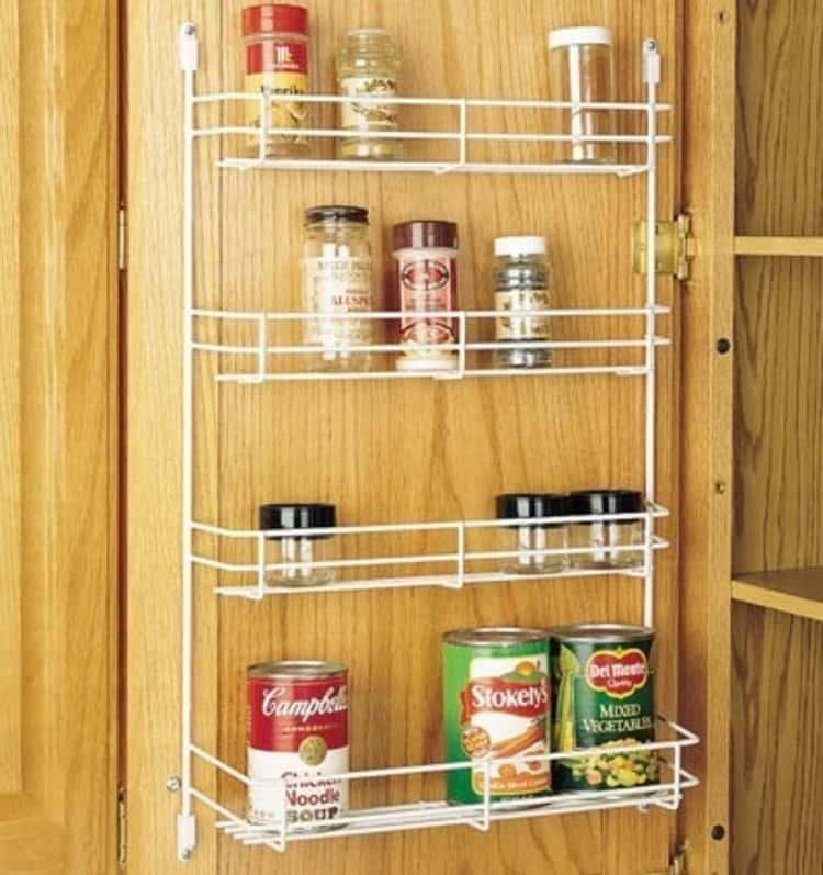 white rack inside a cabinet door holding spices and canned goods