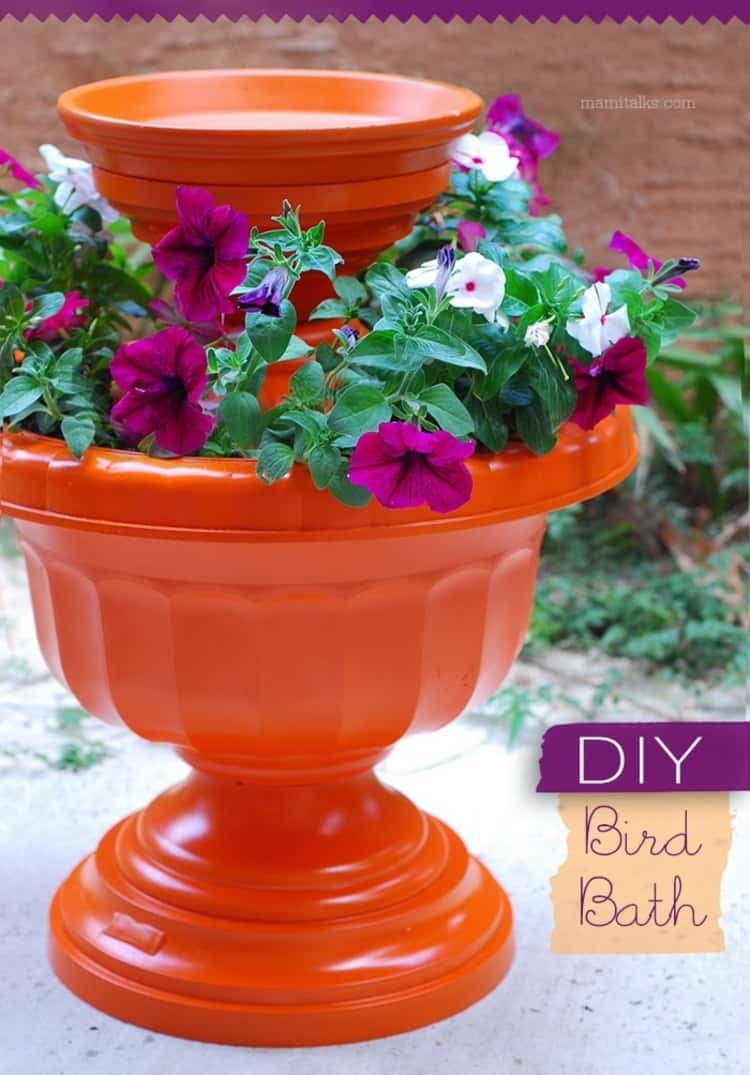 A pretty birdbath made from terra-cotta pots and urns with flowers around it