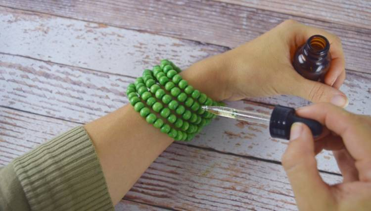 Genius essential oils tips and tricks - image of essential oil dropper applying oil to wooden bead diffuser bracelet
