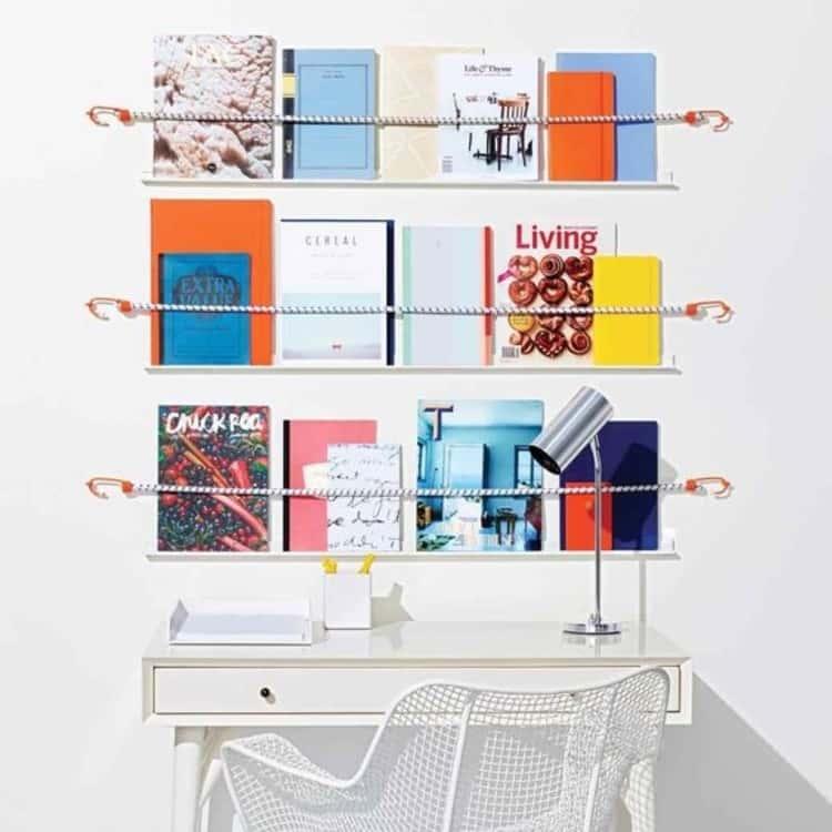 DIY magazine shelf made using bungee cords above a desk