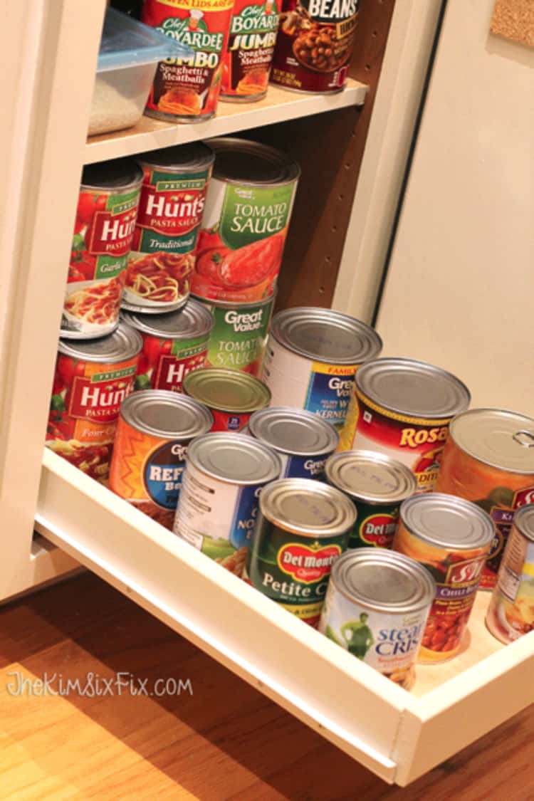 pull out drawer in a cabinet with canned food stored and stacked on it