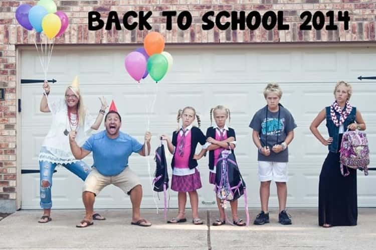back to school photo ideas -  2 parents celebrate back to school while 4 kids stand there looking unhappy