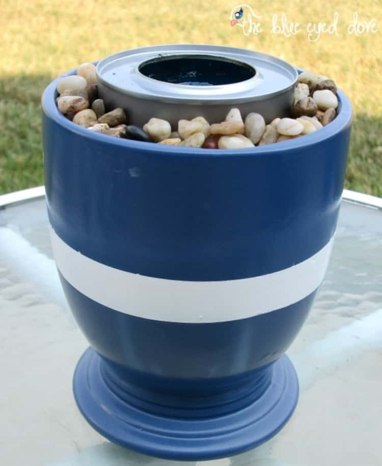 A flowerpot transformed into a fire pit with a can and a few small stones