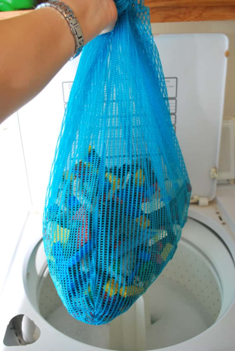 person's hand holding blue laundry bag that contains multi-colored lego pieces