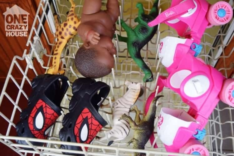 assorted house items and toys on dishwasher rack