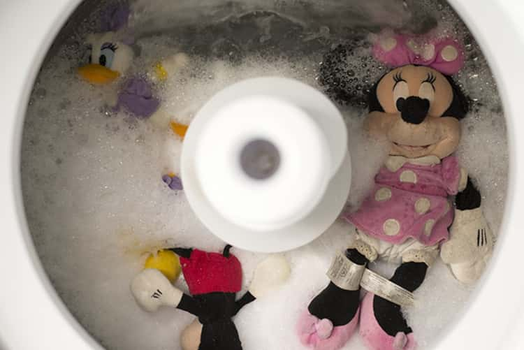 assorted stuffed toys inside soapy water in the washing machine