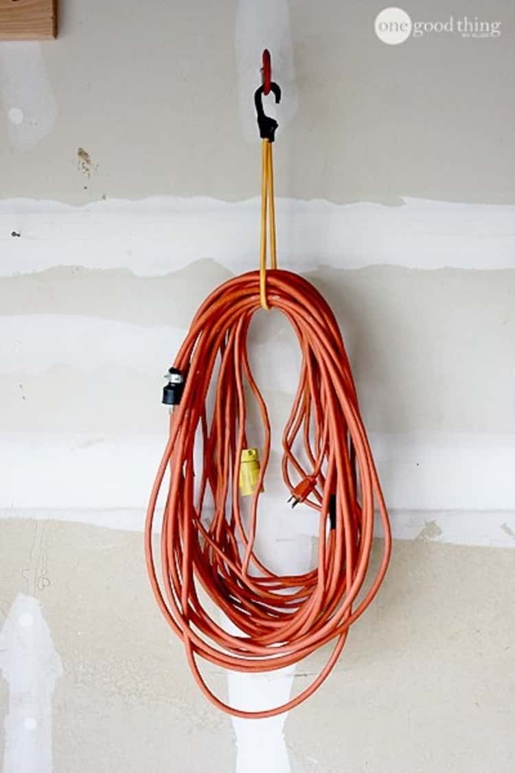 industrial extension cord hung using a bungee cord on a bike hook