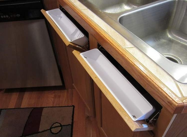 Fake drawers that are attached to front of sink. Just what you need to store extra sponges and cleaning tools in small kitchen areas.