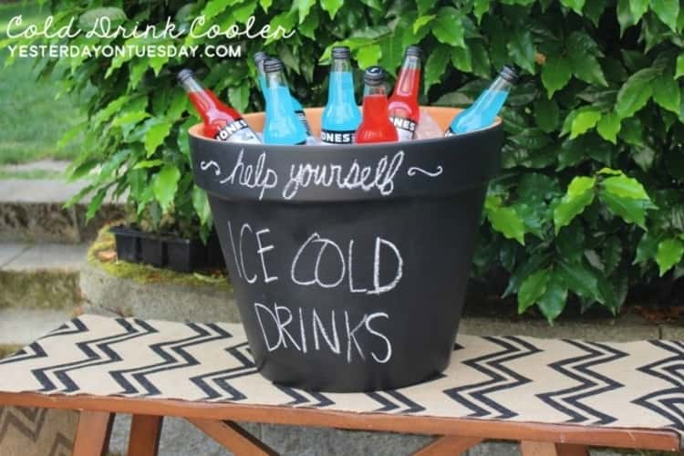 A jumbo flowerpot used to keep cold drinks cool during a summer party