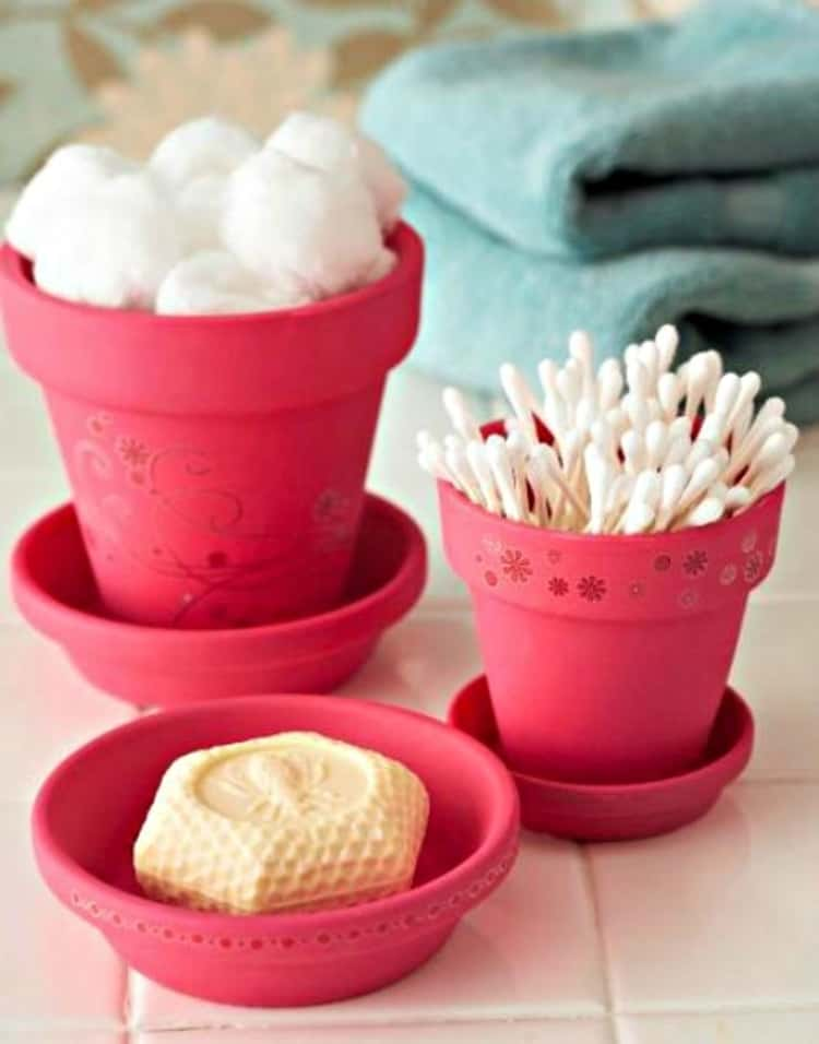 Bathroom organizers made from flower pots holding cotton balls, soap and q-tips