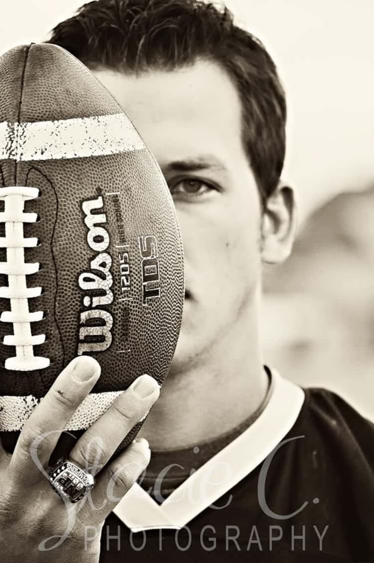 senior picture idea for guys - guy's face partially hidden by a football he's holding upright in front of his face.