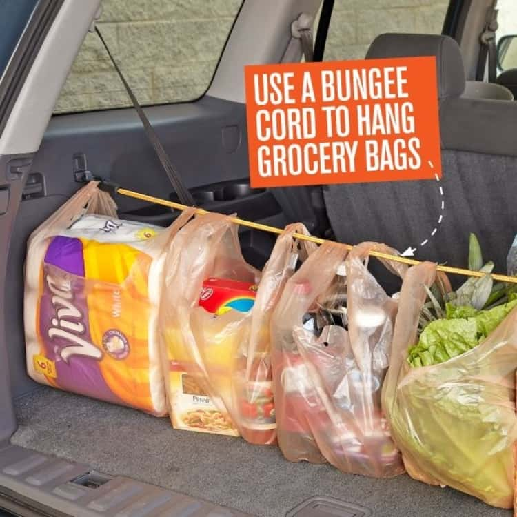 bungee cord uses - a bungee cord in use to hang grocery bags in the trunk