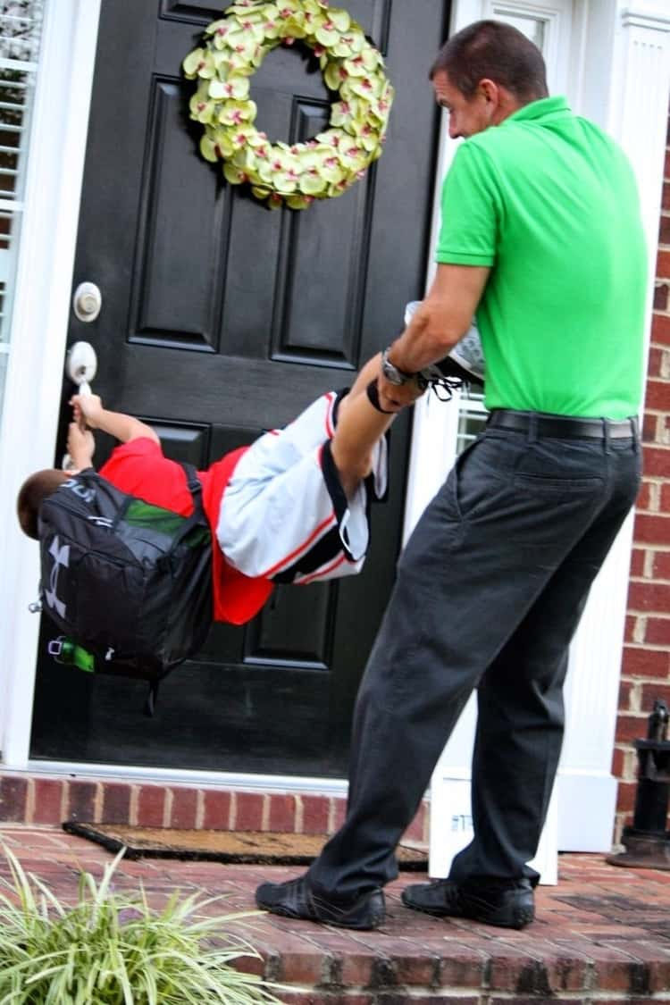 back to school photo ideas - kid hanging on to the doorknob for dear life while dad pulls him off to go back to school
