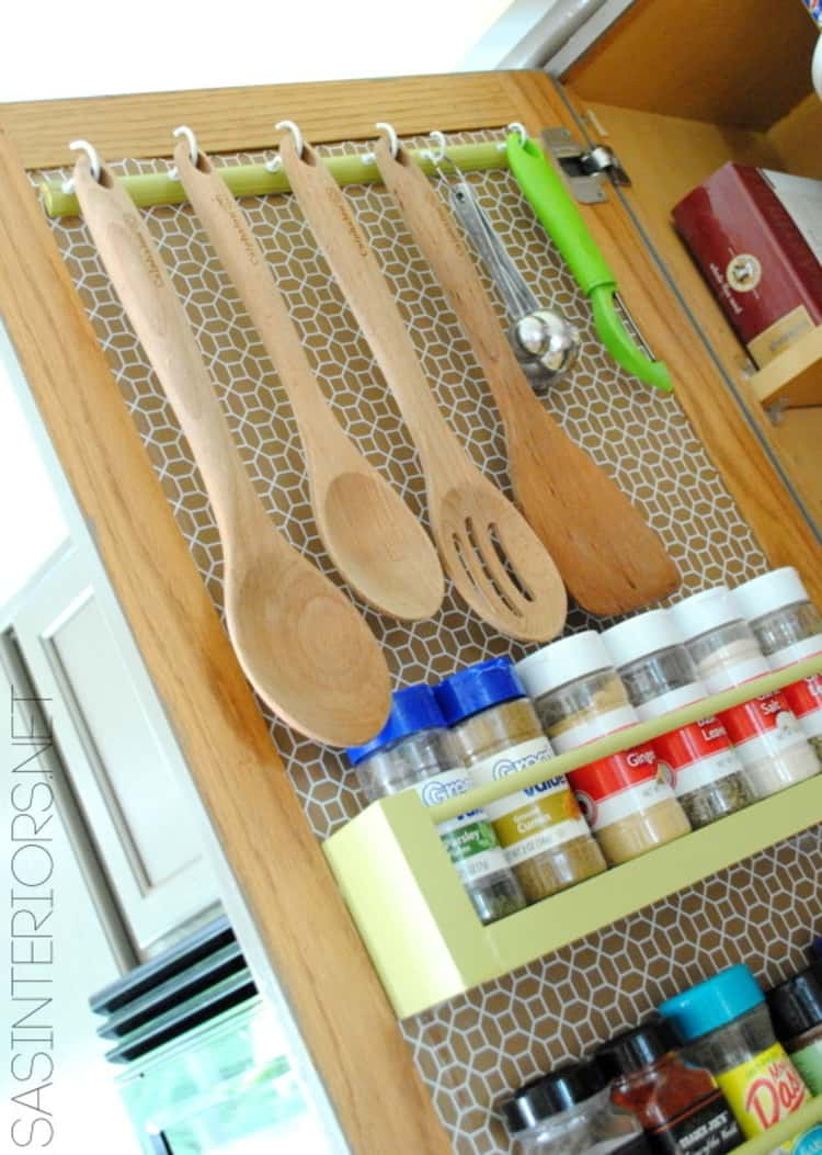 hanging utensils inside a cabinet door with spices underneath