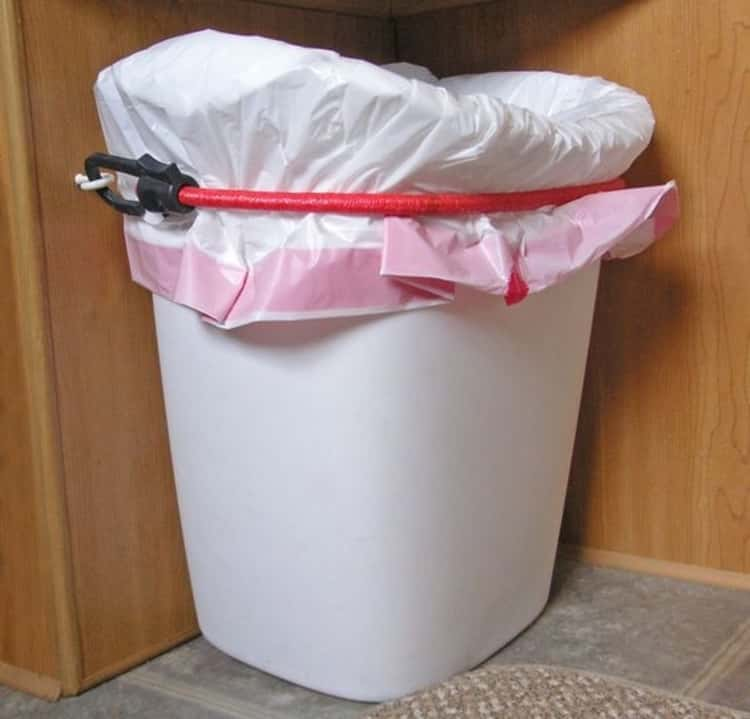 bungee cord uses - trash can held in place using command hooks and a bungee cord