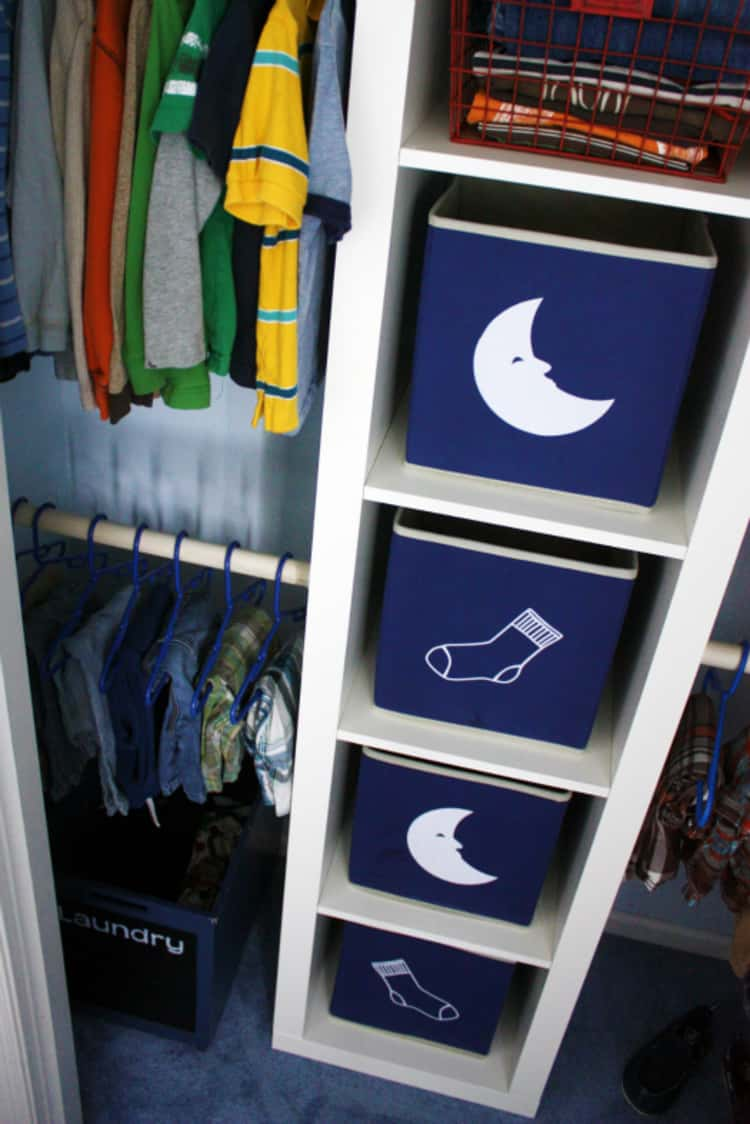 a young boy's closet with 2 clothing bins with a moon image to store pyjamas and two clothing bins with a sock image to store socks