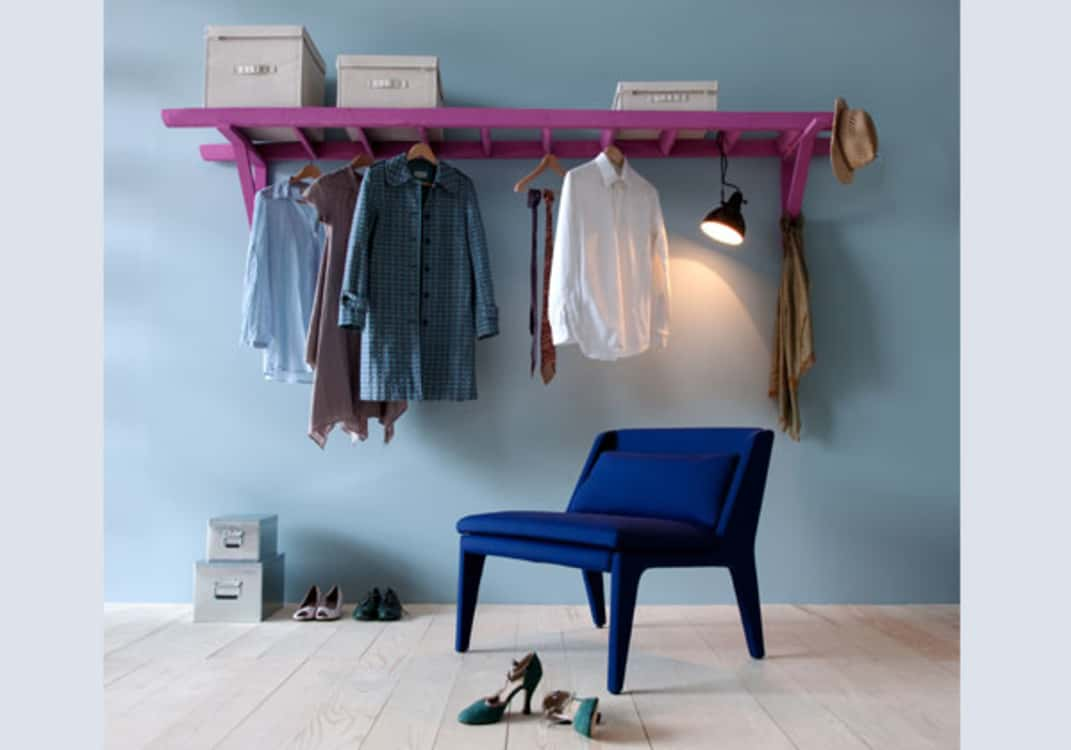 As a way to store clothes and accessories, affix a ladder horizontally on wall. This creates a shelf and hanging space.