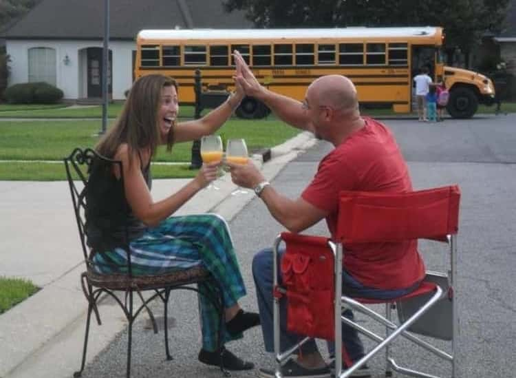 back to school photo ideas - parents celebrating with high fives and drinks as kids get on the school bus