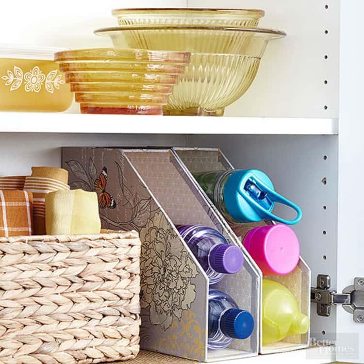 water bottle organization hack using magazine holders in a kitchen cabinet