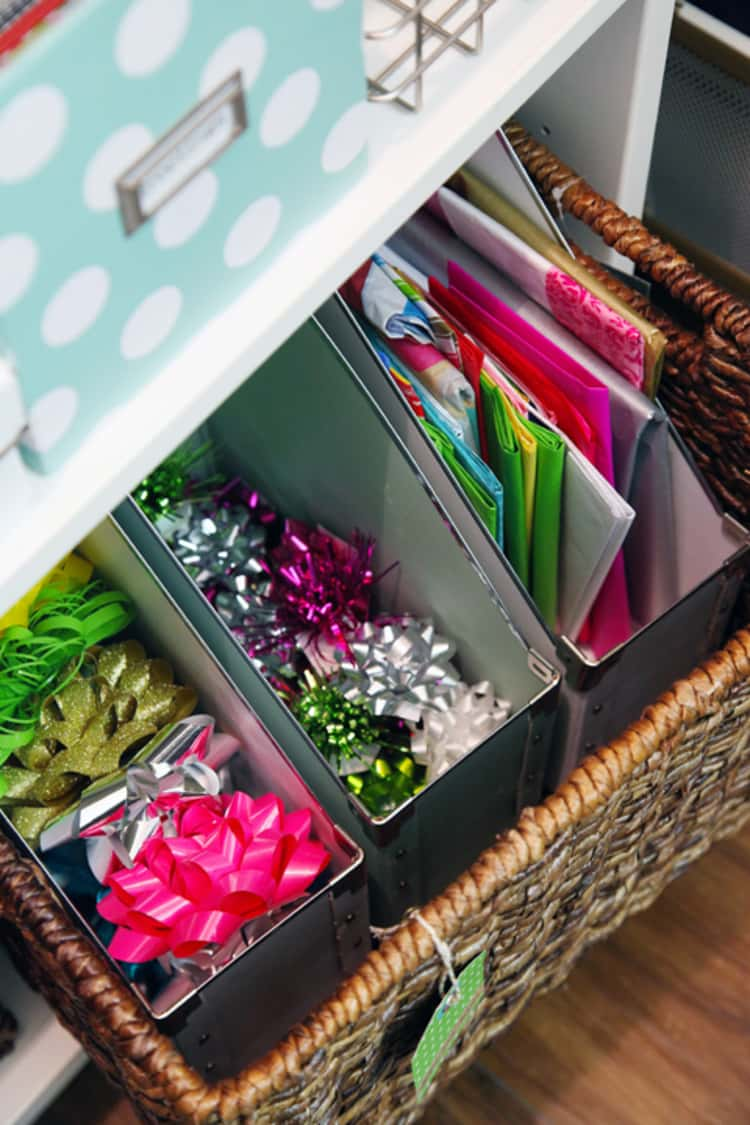 DIY gift wrap station of bows and wrapping paper contained in 3 magazine folders