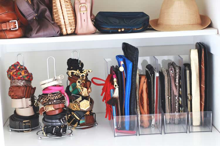 closet showing organized accessories including clutch bags in a clear magazine holder