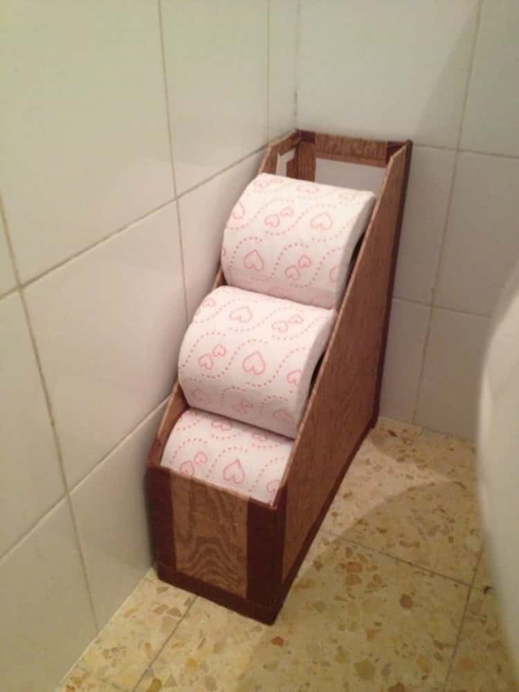 a magazine holder full of toilet rolls that's placed on the bathroom floor