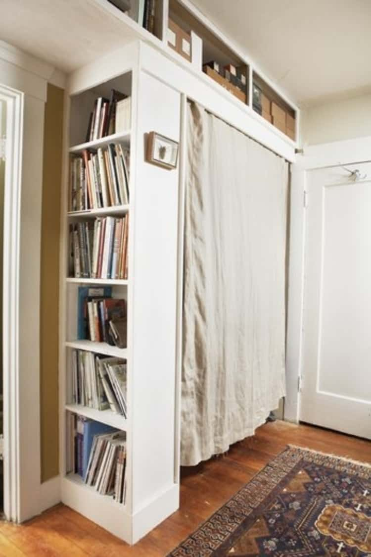 Store your clothes in a closet created with bookshelf and curtain hung between bookshelf and wall