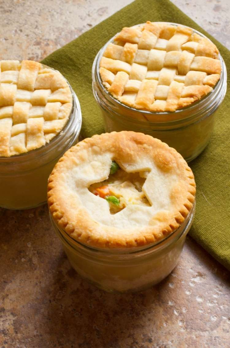 Chicken pot pie: 3 small containers filled with chicken pot pie.- 2 pies covered with woven crust, 1 mason jar pie with a star crust cut-out
