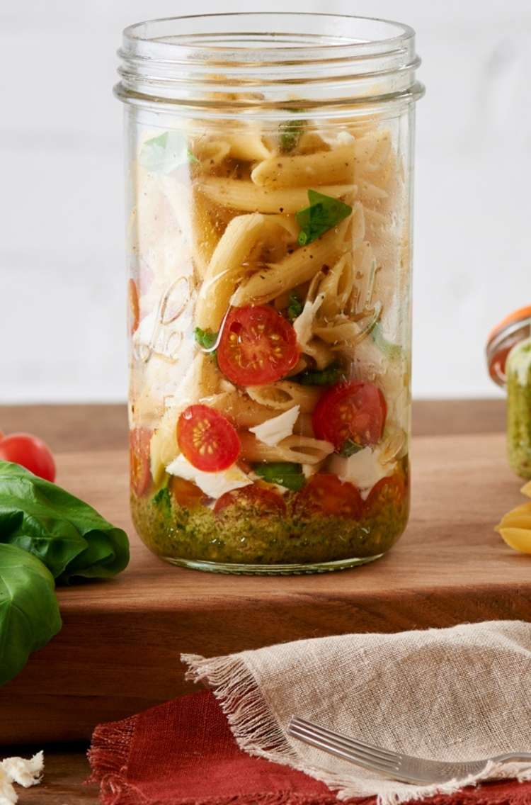 Pasta to go: jar with penne pasta noodles, red cherry tomatos, and green vegetables,