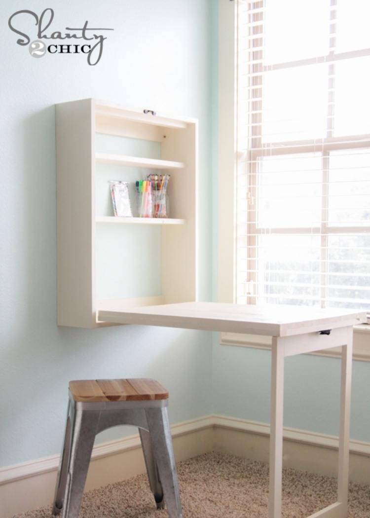 Pull out white murphy desk with bar stool. This desk stows away perfectly to give you more space in small offices when needed.