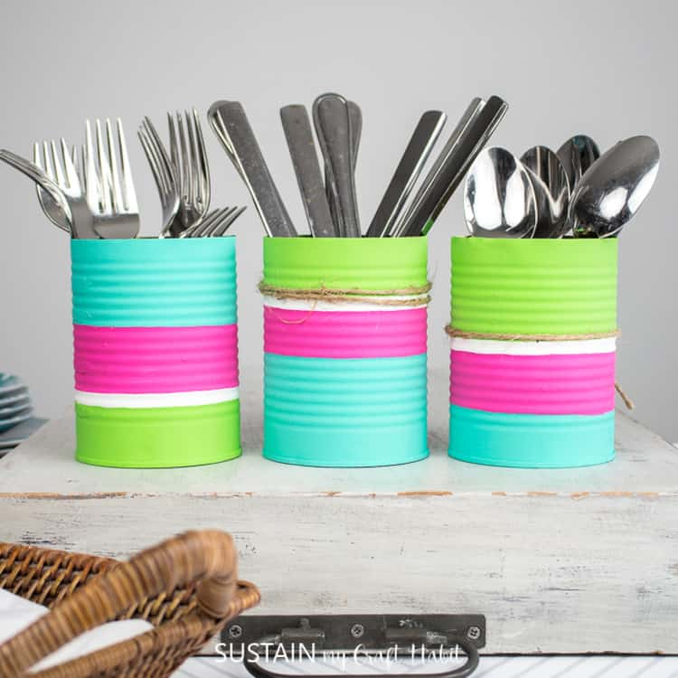 painted tin cans serving as utensil organizers