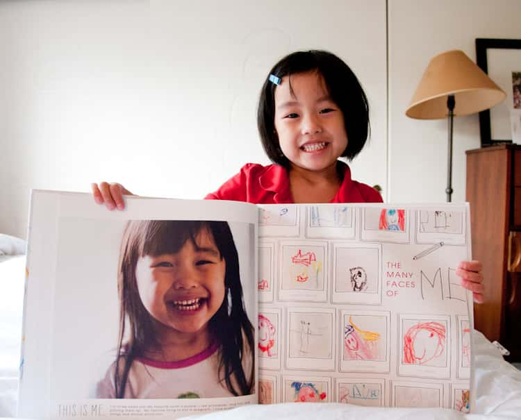 little girl holding a photo book with her on one page and her artwork on another