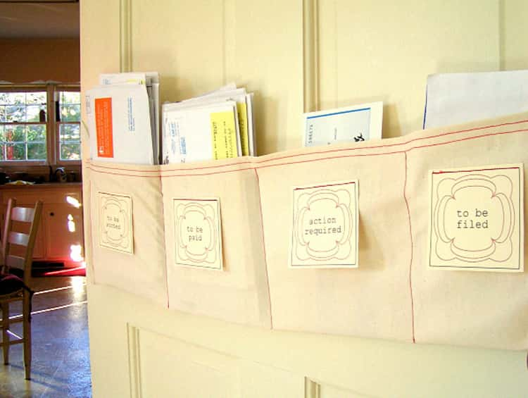 DIY paper sorter hung on the wall with letters inside, beige color