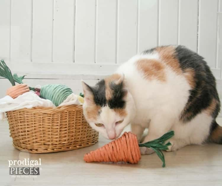 a cat playing with one of it's DIY paper mache cat toys that resembles a carrot
