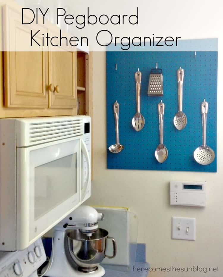 blue pegboard hanging on kitchen wall with spoons hanging on it, a microwave to the left of it