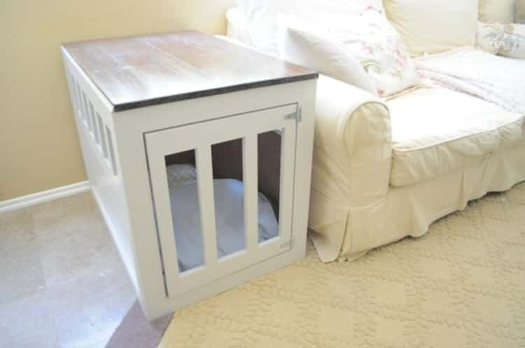 A wooden dog crate doubling as an end table placed at the end of a couch