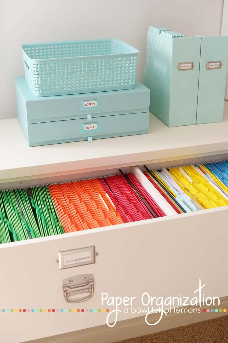colored file folders in a big drawer for incoming paper to be filed. blue baskets on top of drawer.