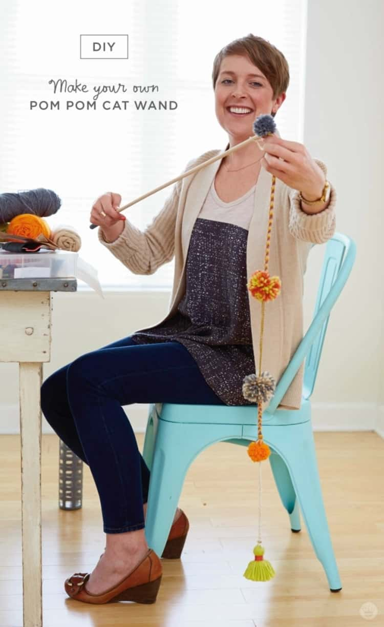 woman seated and holding a DIY pom-pom cat wand