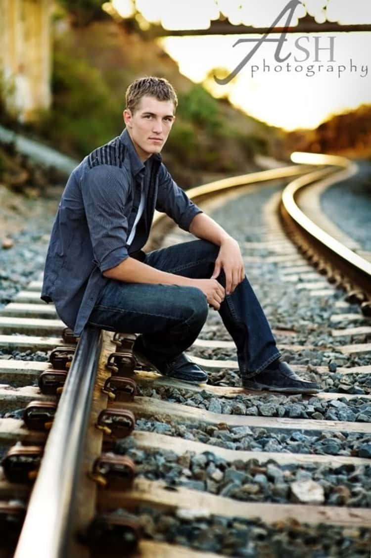 senior picture ideas for guys - guy posing for a photo while seating on an empty railroad track