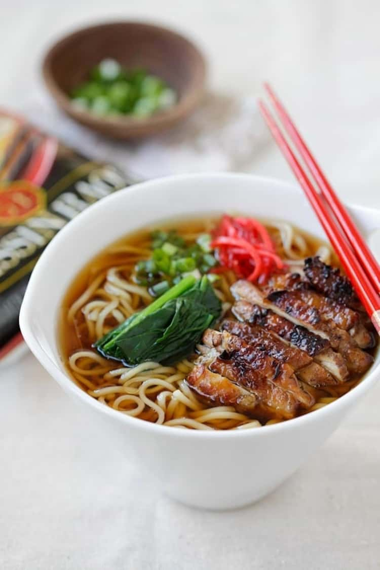 A bowl of ramen noodles in soy sauce with pieces of chicken topped with lemongrass and two chopsticks