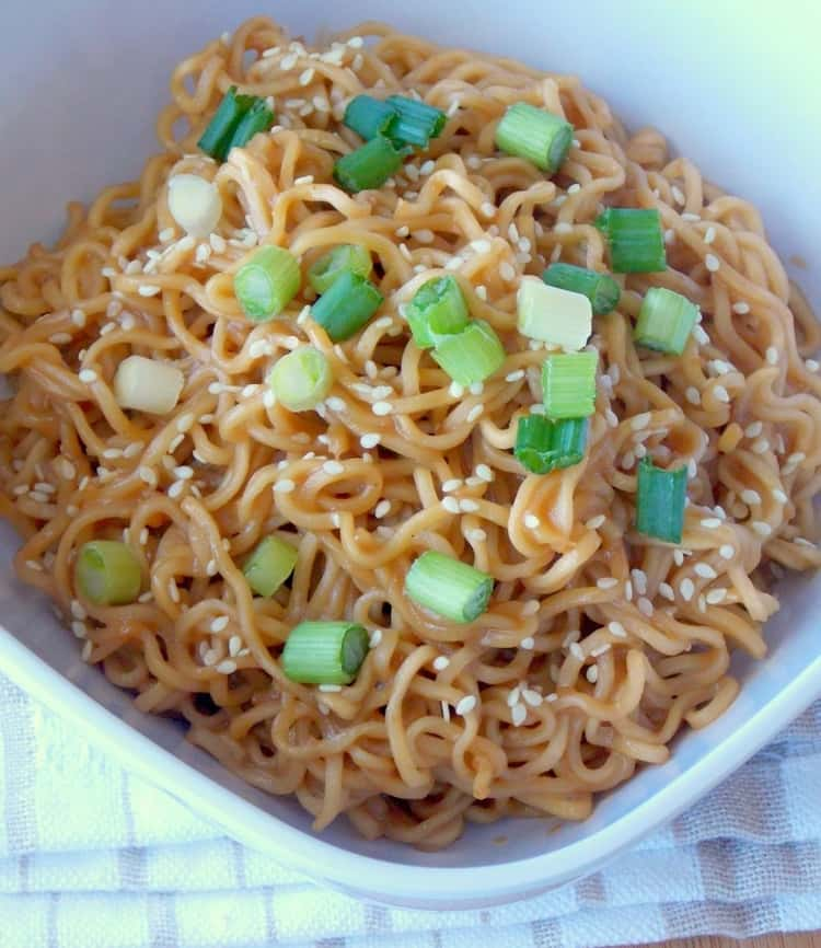 A plate of ramen noodles tossed in peanut butter sauce and topped with some sesame seeds and green onions