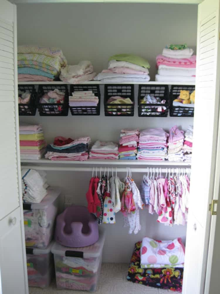 a children's closet with hanging baskets under the closet rod to organize their smaller clothing items