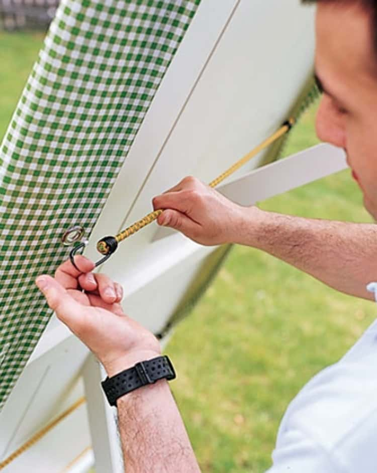 bungee cord uses - person anchoring down the table cloth using grommets and a bungee cord