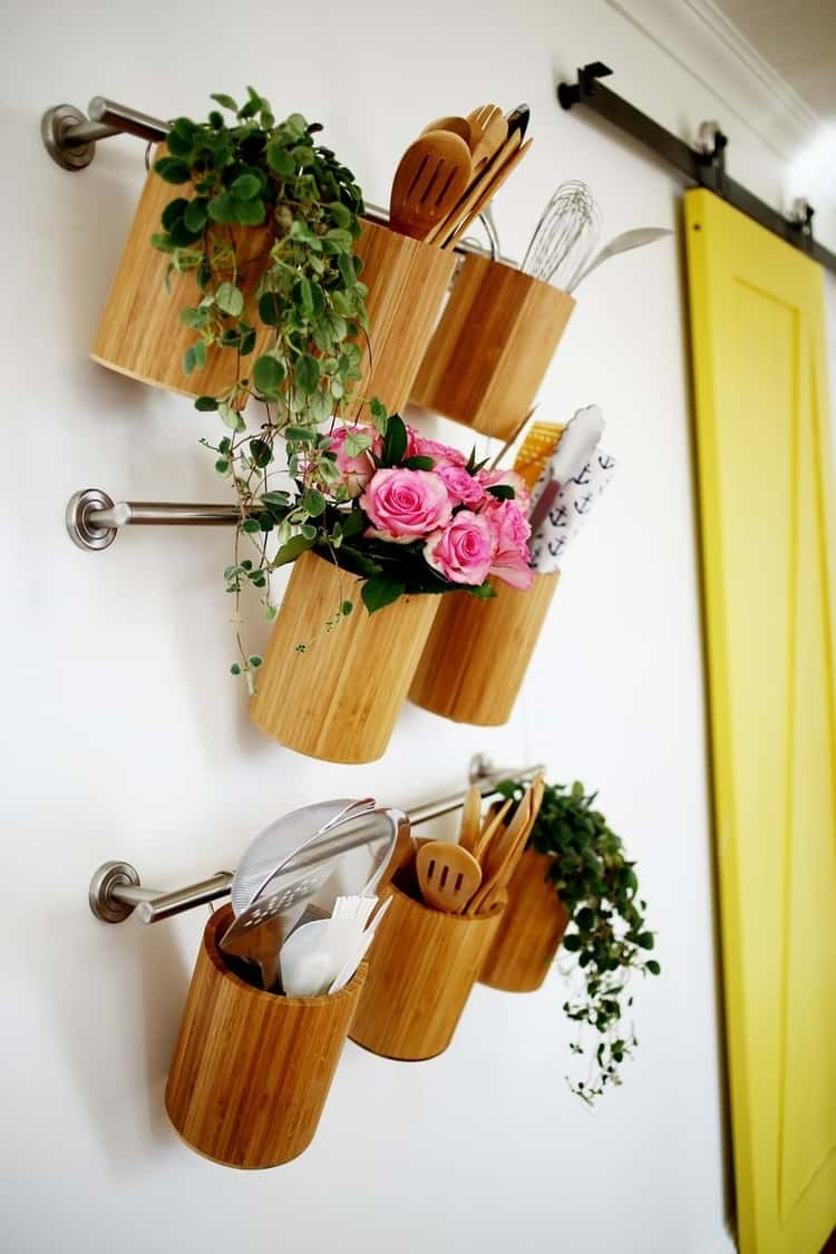 3 towel bars hanging on the wall on top of each other with canisters hung on them and utensils inside, a couple of them with flowers