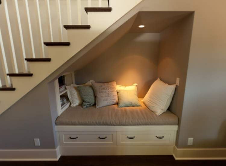 under the stairs reading nook with pillows. Great repurposing idea for tiny rooms.