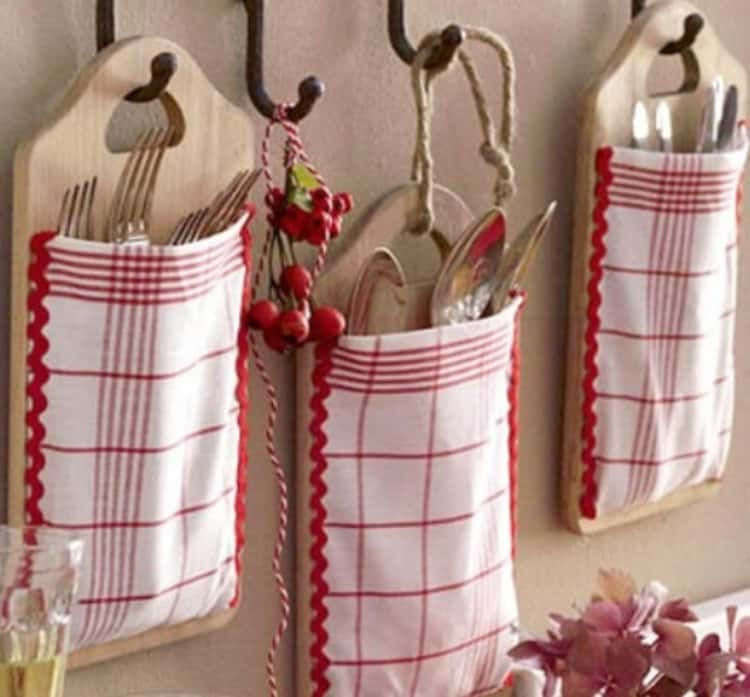 3 cutting boards with kitchen towels attached, hanging on the wall holding kitchen utensils