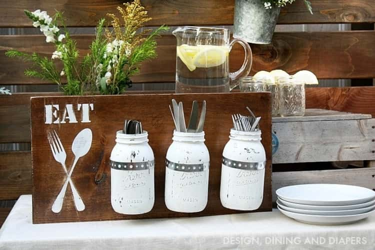 utensil organization in white painted mason jars attached to a piece of wood with EAT and utensils painted on it