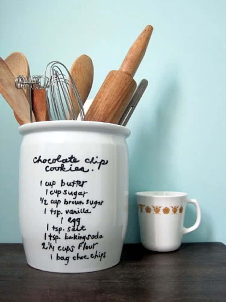 white vase with chocolate chip cookie recipe written on outside and kitchen utensils inside